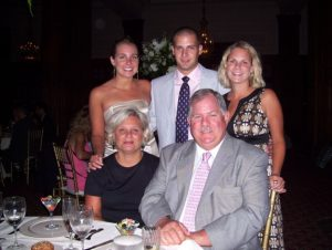 Charles Grugan, center, stands with his two sisters, Carolyn Grugan Noll, left, and Jennifer Grugan Whitehouse, right. Charles' mother, Eileen Grugan and his father, Charles Grugan Sr. sit in the front. (Courtesy/Carolyn Grugan)